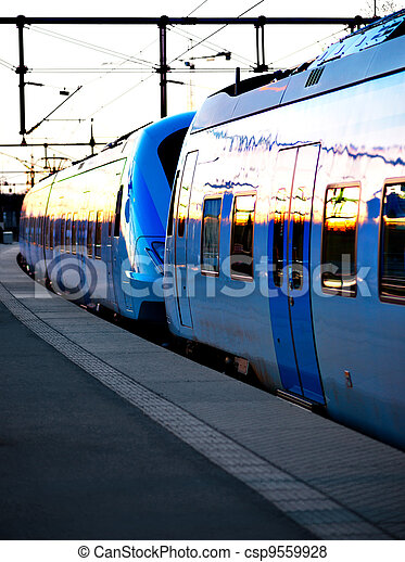 Blue commuter train in evening light at station - csp9559928
