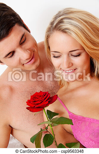 couple in bed with rose. proposal - csp9563348
