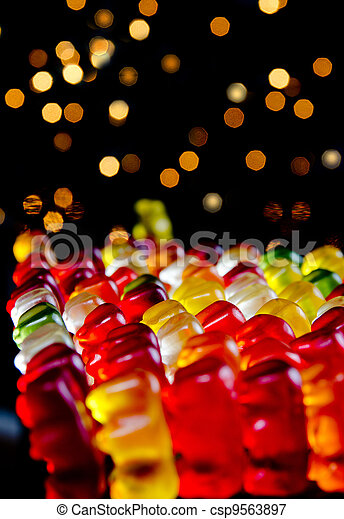 Army of sweet colorful jelly teddies with blinking lights on black background - csp9563897