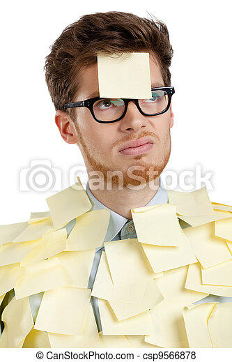 Unhappy young man with a sticky note on his face, covered with yellow stickers - csp9566878