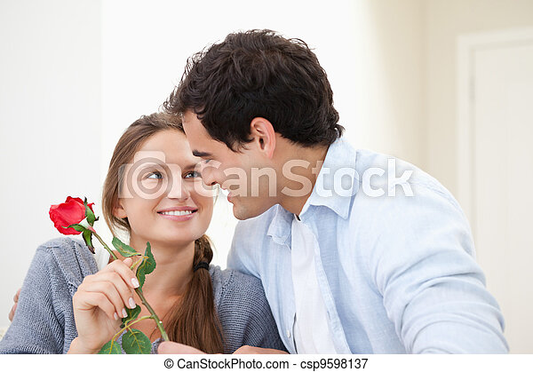 Man offering a rose to a Woman while embracing indoors - csp9598137