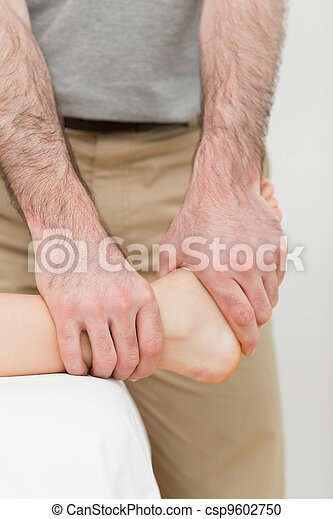 Osteopath manipulating the ankle of a patient - csp9602750