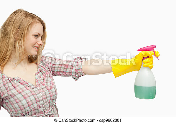 Blond-haired woman holding a spray bottle - csp9602801