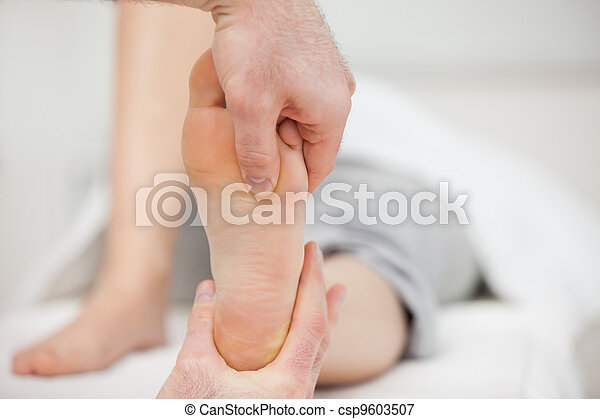 Practitioner placing his thumb on a foot - csp9603507