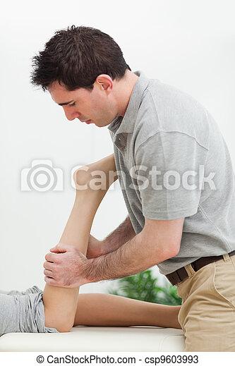 serious masseur massaging the leg of a woman - csp9603993