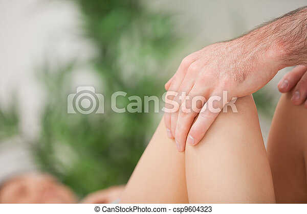 Legs being held by a practitioner - csp9604323