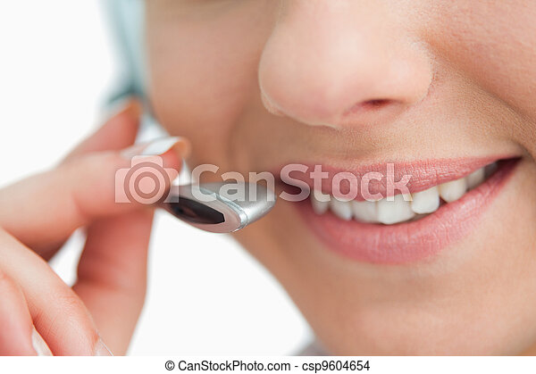 Close-up on a smiling businesswoman mouth speaking in headset  - csp9604654