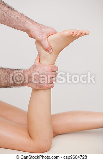 Podiatrist manipulating the ankle of his patient - csp9604728