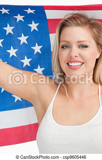 Smiling woman holding the Old Glory flag - csp9605446