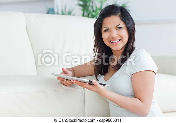 Smiling woman holding a tactile tablet in front of a sofa - csp9606011