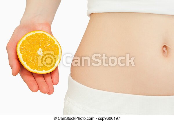Woman placing an orange near her belly - csp9606197