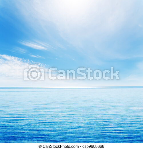 light waves on blue sea and cloudy sky with sun - csp9608666