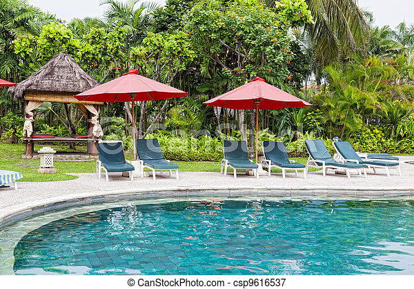 Chaise lounges at pool in hotel in tropics - csp9616537