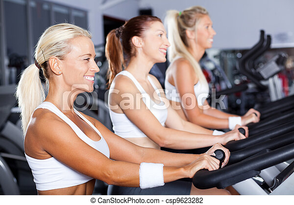 group of young women cycling in gym - csp9623282