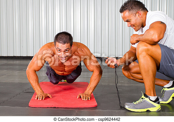 fitness man and personal trainer in gym - csp9624442