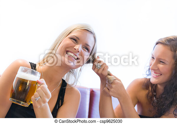 Two girls fighting over beer in restaurant - csp9625030