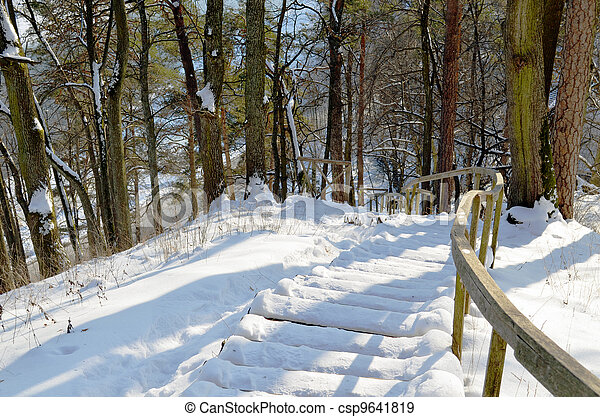 Wooden snowy oak staircase with handrail on steep hill in winter - csp9641819