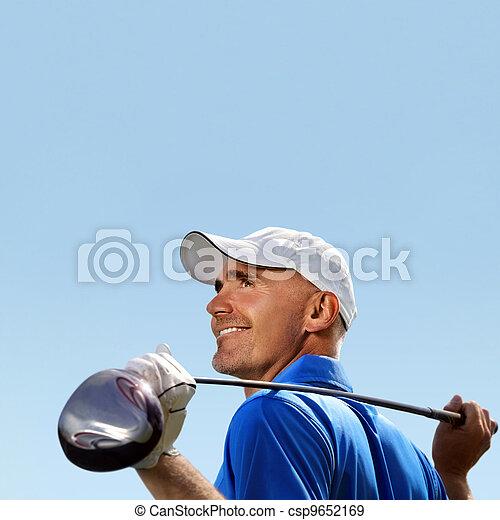 Smiling golfer holding golf club over shoulder - csp9652169