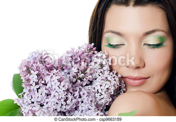 Beautiful woman with spring flowers of a lilac. Skincare - csp9663189