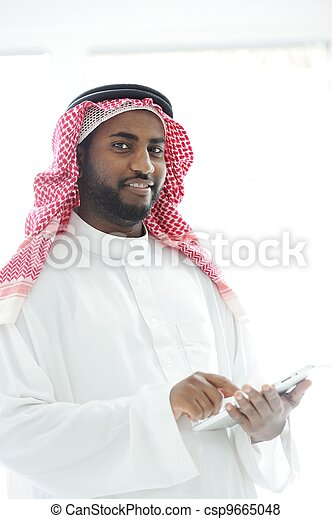 Middle eastern man with gulf clothes using tablet at office - csp9665048