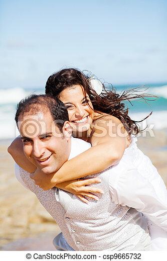 happy groom and bride piggyback on beach  - csp9665732