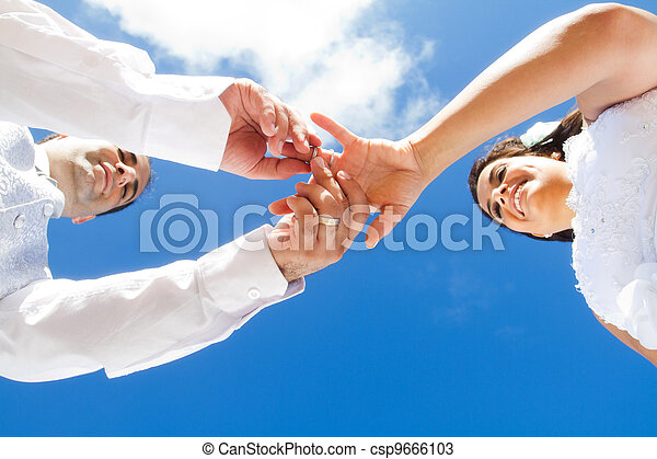 groom putting wedding on bride - csp9666103