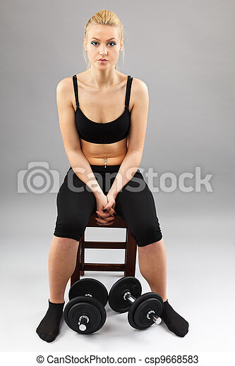 Athletic young lady working out with weights - csp9668583