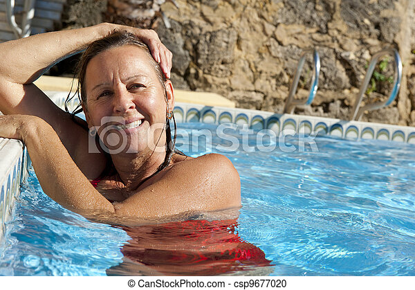 Happy mature woman in pool - csp9677020