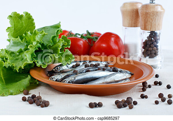 Anchovy fish on a plate with herbs lettuce, branch of tomatoes and spicy peppers - csp9685297