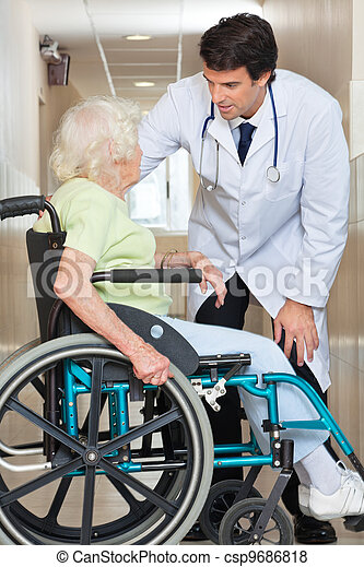 Doctor Communicating With Senior Woman Sitting In Wheelchair - csp9686818