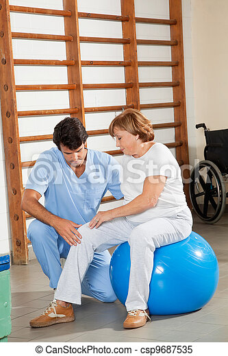 Therapist Examining Senior Woman's Knee - csp9687535