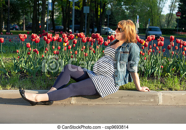 Pregnant woman sitting near tulip flowerbed - csp9693814