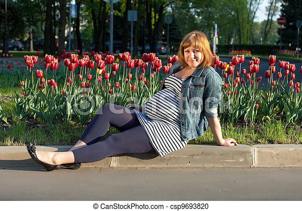 Pregnant woman sitting near tulip flowerbed - csp9693820
