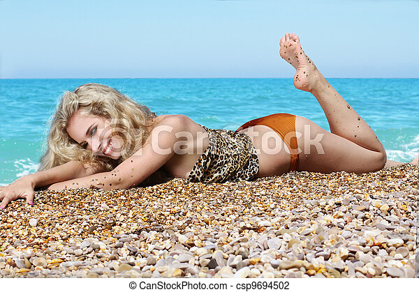 Summer beach happy woman sunbathing in bikini alone - csp9694502