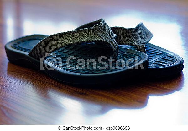 Flip Flops on Hardwood Floor - csp9696638