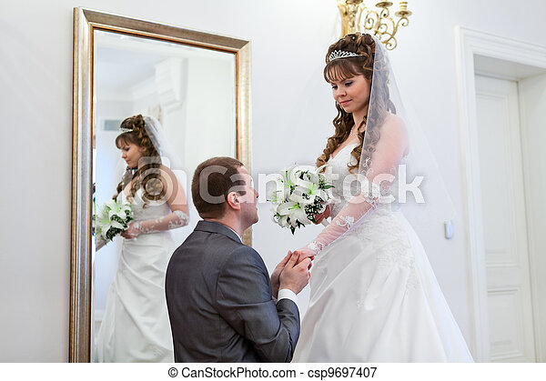 Young wedding Caucasian Russian couple. Groom kissing hand of bride - csp9697407