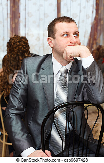 Tired Caucasian Russian bridegroom waiting for bride during wedding preparations in domestic room - csp9697428