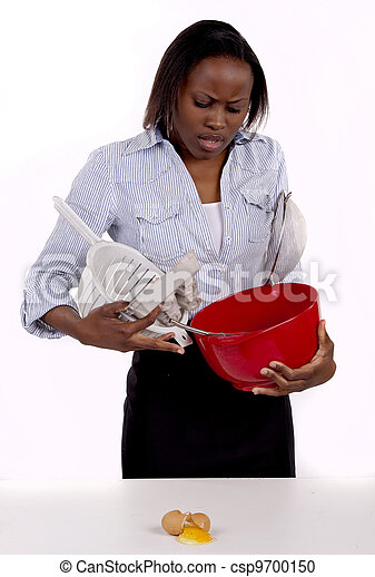 South African woman struggling with a mess she made in the kitchen. - csp9700150