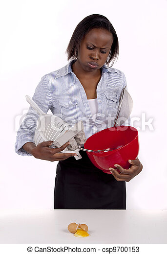South African woman struggling with a mess she made in the kitchen. - csp9700153