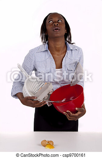 South African woman struggling with a mess she made in the kitchen. - csp9700161