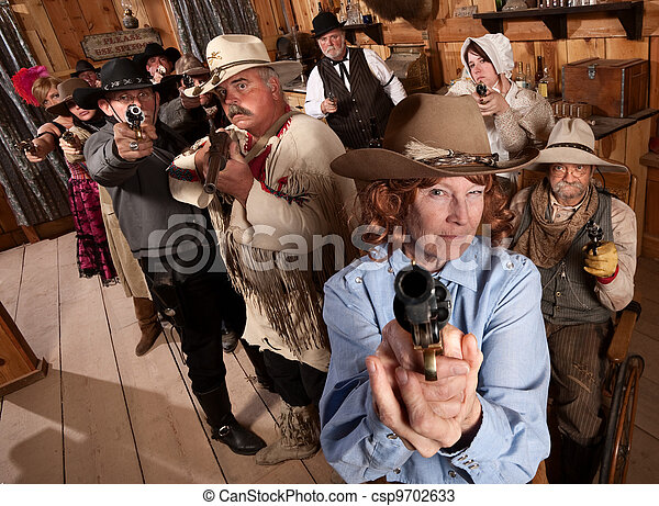 Group of Cowboys Point Guns in Bar - csp9702633