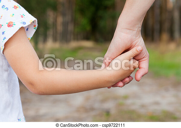Mother holding a hand of his doughter outdoors