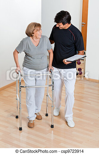 Trainer Looking At Senior Woman Using Walker - csp9723914