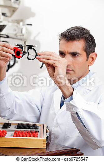 Eye Doctor Checking Lens Of Trial Frames - csp9725547
