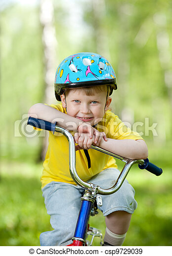 nice kid weared in helmet on bicycle - csp9729039