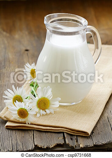 pitcher of milk on a wooden table - csp9731668