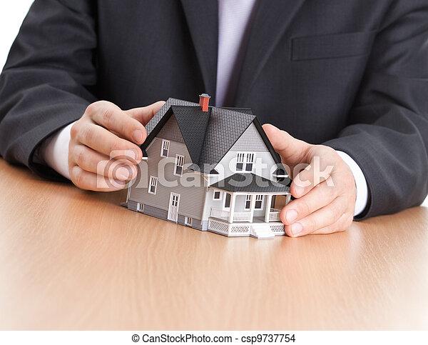 Businessman hands around household architectural model - csp9737754