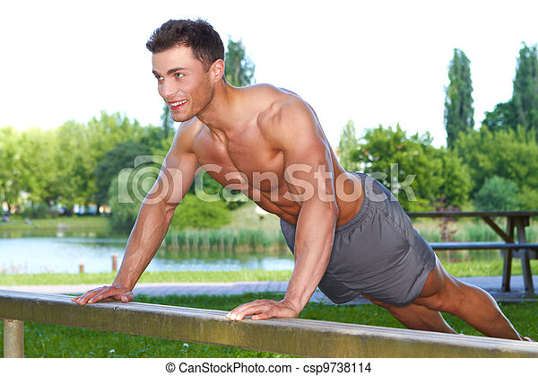 Fitness man in park making push ups - csp9738114