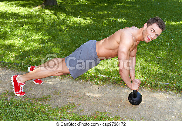 Handsome man exercises with kettlebell - csp9738172