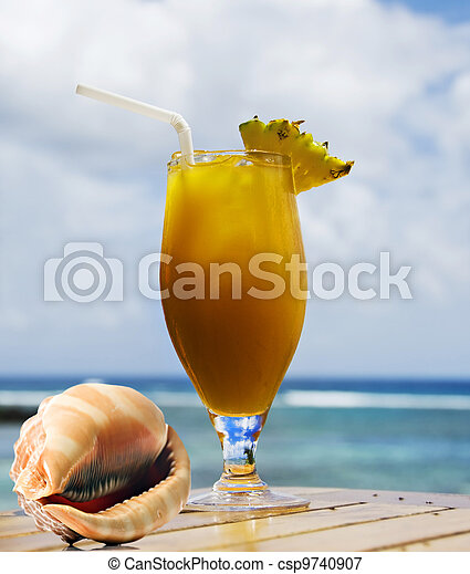 Tropical fruit cocktail and sea shell with ocean in background - csp9740907